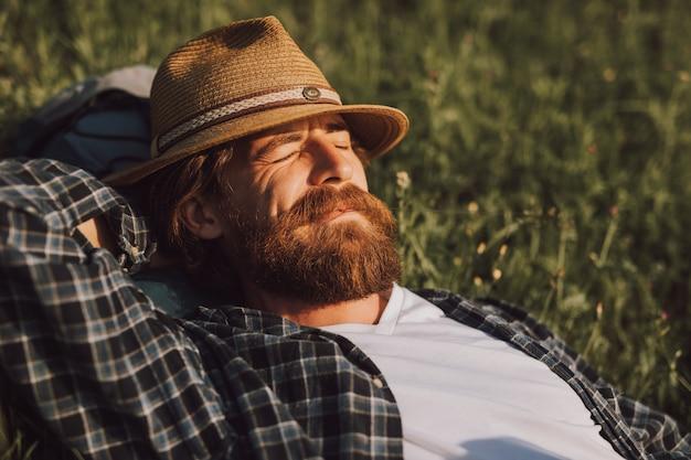 Hombre barbudo despreocupado relajado relajándose sobre el césped