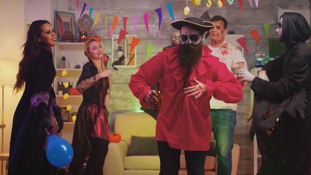 Hombre barbudo disfrazado de pirata celebrando halloween con sus amigos en una sala de fiestas decorada temáticamente