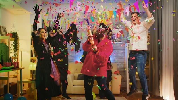 Hombre barbudo disfrazado de pirata en la fiesta de halloween soplando confeti mientras sus amigos se divierten en el fondo. disparo en cámara lenta