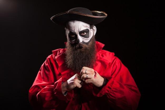 Hombre barbudo disfrazado de pirata peligroso sobre fondo negro.