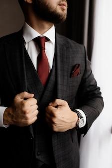 Hombre barbudo con elegante esmoquin y corbata roja, manos fuertes de hombre