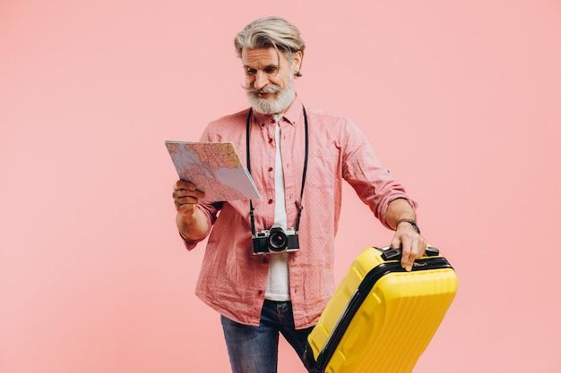 Hombre barbudo elegante sostiene una maleta amarilla y elige un país para viajar en el mapa.