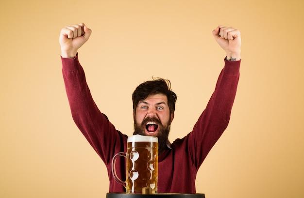 Hombre barbudo emocionado con cerveza cerveza feliz cervecero con vaso con cerveza hombre degustación de cerveza de barril