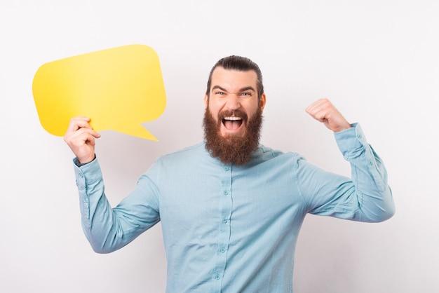 Hombre barbudo emocionado está haciendo el gesto de ganador y sosteniendo un bocadillo.