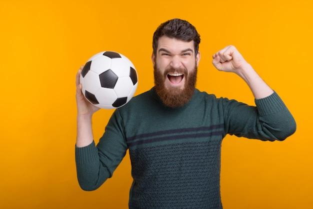 Hombre barbudo emocionado que sostiene una bola en su mano mientras que grita y hace gesto del ganador en espacio amarillo.