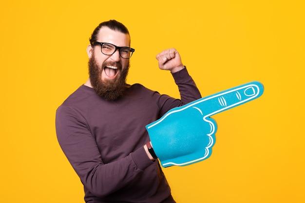 Hombre barbudo emocionado sosteniendo un guante apuntando hacia afuera