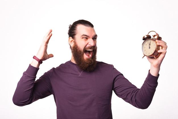 Hombre barbudo emocionado está sosteniendo y mirando el reloj