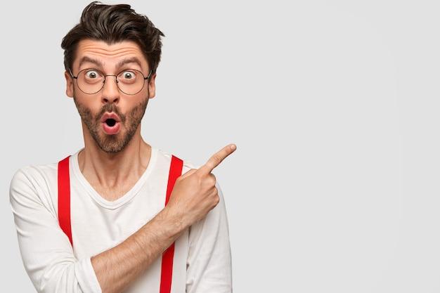 Hombre barbudo emocional tiene expresión facial sorprendida, mirada asombrada, vestido con camisa blanca con tirantes rojos, puntos con el dedo índice en la esquina superior derecha