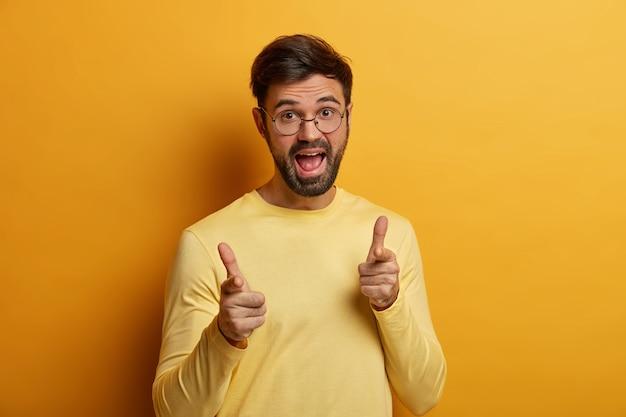 Hombre barbudo encantado positivo que le atrae, señala con el dedo, hace una buena elección, tiene una expresión divertida y alegre, elige a alguien, le muestra su gesto, elige a un cliente potencial