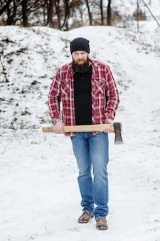 Hombre barbudo enojado con un hacha atraviesa el bosque de invierno