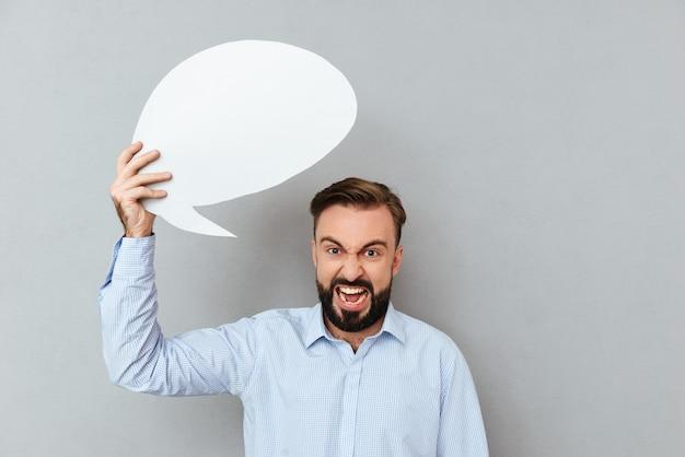 Hombre barbudo enojado en ropa de negocios con bocadillo en blanco