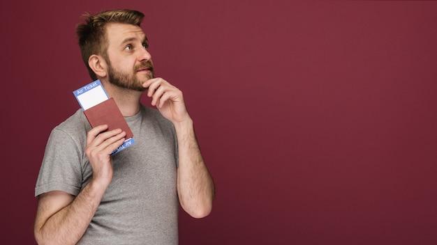 Hombre barbudo de ensueño en una camiseta con billetes de avión y pasaporte sobre un fondo rubí
