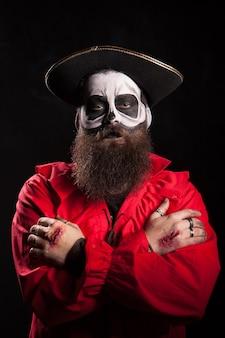 Hombre barbudo espeluznante con traje de pirata para halloween mirando a la cámara sobre fondo negro.