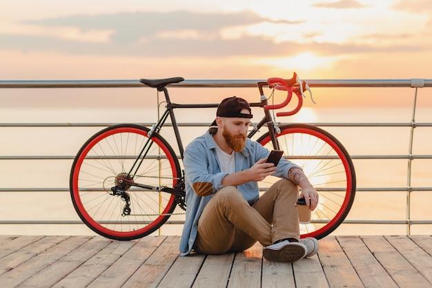 Hombre barbudo de estilo hipster guapo con camisa vaquera y gorra con smartphone con bicicleta en el amanecer de la mañana junto al mar tomando café, viajero de estilo de vida activo y saludable