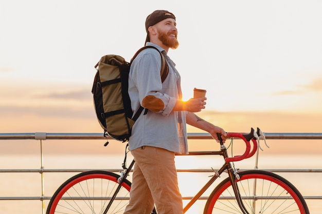 Hombre barbudo de estilo hipster guapo con mochila con camisa de mezclilla y gorra con bicicleta en el amanecer de la mañana junto al mar tomando café, mochilero viajero de estilo de vida activo y saludable