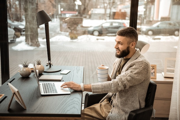 Hombre barbudo expresivo con una taza de café en sus manos trabajando en una computadora portátil delgada