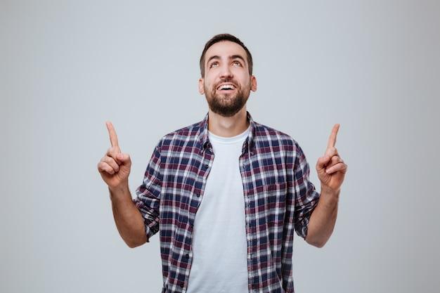 Hombre barbudo feliz en camisa apuntando hacia arriba