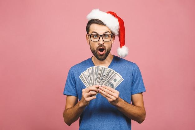 Hombre barbudo feliz en casual y sombrero de navidad con dinero