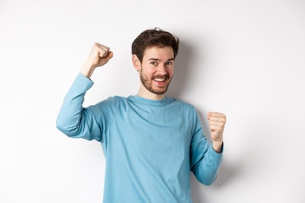 Hombre barbudo feliz celebrando la victoria, levantando las manos y triunfando, ganando el premio y sonriendo con alegría, de pie sobre fondo blanco.