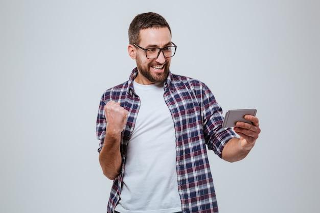 Hombre barbudo feliz en eyeglases mirando el teléfono