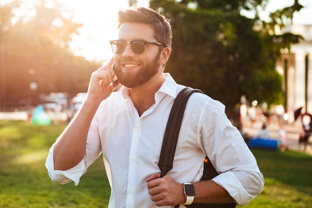 Hombre barbudo feliz en gafas de sol de pie al aire libre mientras sostiene la mochila y hablando por teléfono inteligente