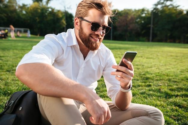 Hombre barbudo feliz en gafas de sol y ropa de negocios sentado en el césped al aire libre y usando su teléfono inteligente