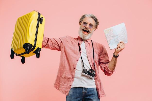 Hombre barbudo feliz en gafas de sol sostiene una maleta y un mapa, canta y baila