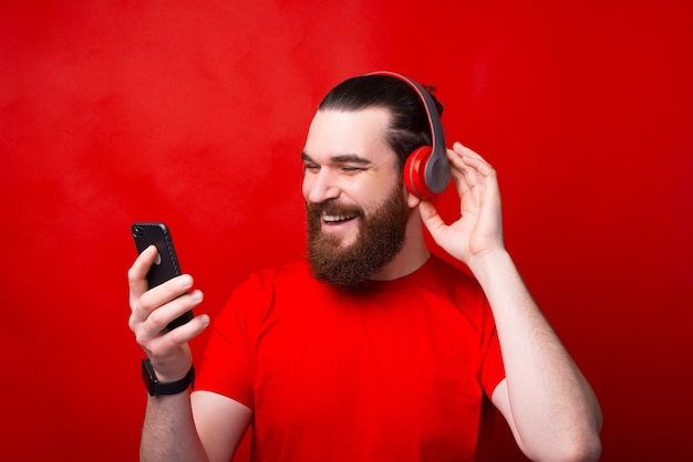 Hombre barbudo feliz joven alegre escuchando música sobre pared roja