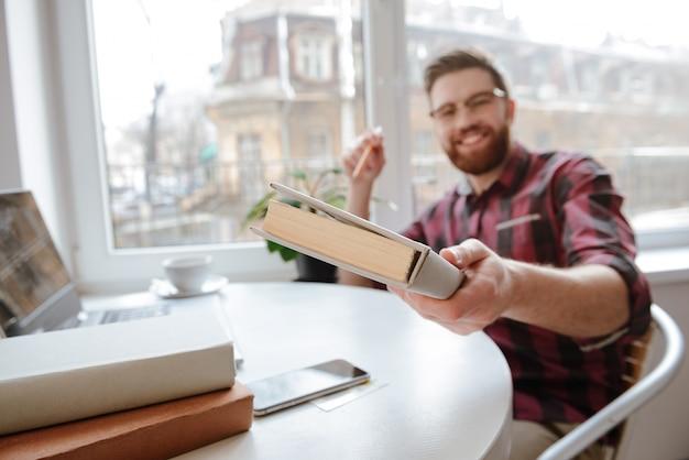 Hombre barbudo feliz que muestra el libro a la cámara. centrarse en el libro.