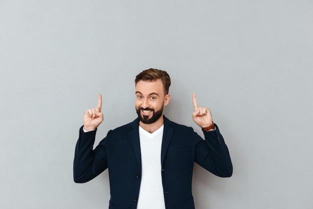 Hombre barbudo feliz en ropa de negocios apuntando hacia arriba y mirando a la cámara sobre gris