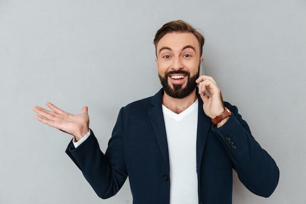 Hombre barbudo feliz en ropa de negocios hablando por teléfono inteligente y agujereando copyspace en la libra mientras mira a la cámara sobre gris