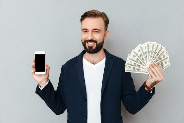 Hombre barbudo feliz en ropa de negocios mostrando dinero y teléfono inteligente