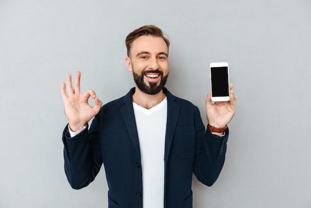 Hombre barbudo feliz en ropa de negocios que muestra la pantalla del teléfono inteligente en blanco