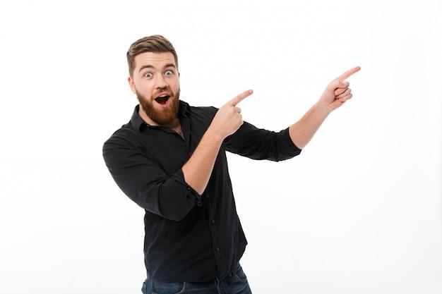 Hombre barbudo feliz sorprendido en camisa apuntando lejos