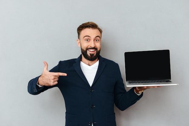 Hombre barbudo feliz sorprendido en ropa de negocios que muestra la pantalla de la computadora portátil en blanco y apuntando a él sobre gris