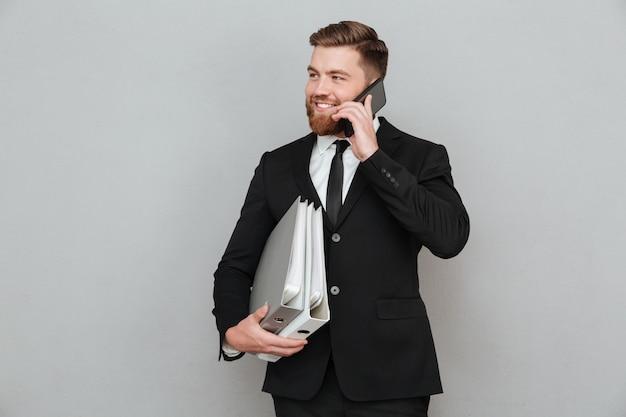 Hombre barbudo feliz en traje hablando por teléfono