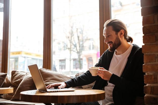 Hombre barbudo feliz usando laptop en café