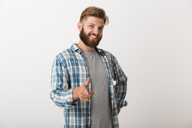 Hombre barbudo feliz vestido con camisa a cuadros que se encuentran aisladas, apuntando a la cámara