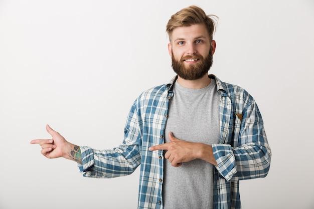 Hombre barbudo feliz vestido con camisa a cuadros que se encuentran aisladas, señalando con el dedo en el espacio de la copia