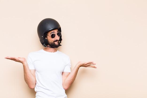 Hombre barbudo fresco joven dudando con un casco