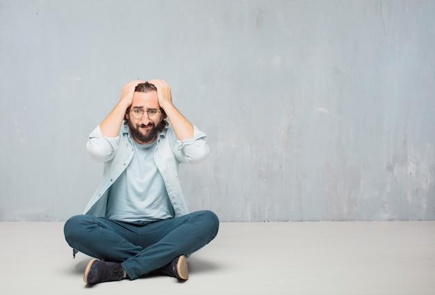 Hombre barbudo fresco joven que se sienta en el piso. fondo de pared grunge