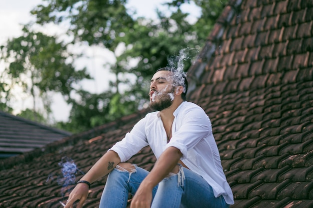 Hombre barbudo fumando en el techo