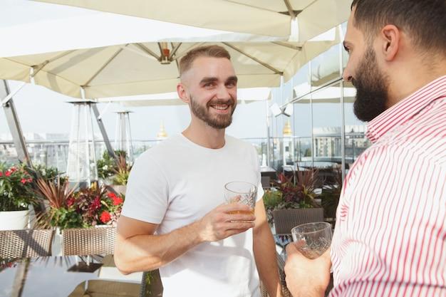 Hombre barbudo guapo alegre sonriendo a la cámara disfrutando de la fiesta de verano en la azotea