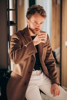Hombre barbudo guapo bebiendo whisky