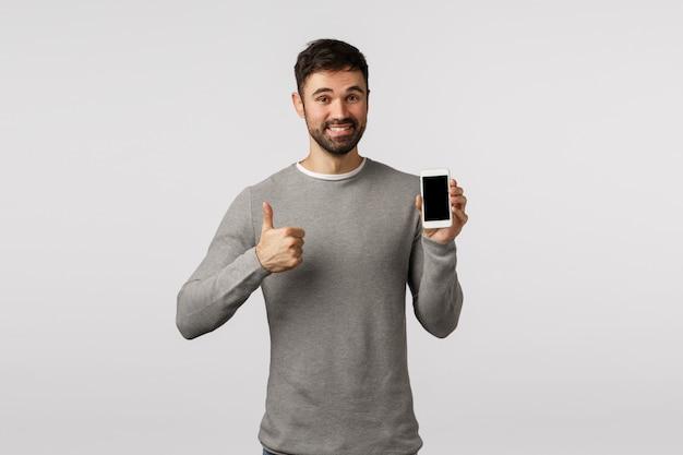 El hombre barbudo guapo y encantado con un suéter gris recomienda usar la aplicación o como nuevo messanger, sitio de compras, sostener el teléfono inteligente, mostrar el pulgar hacia arriba con aprobación, como, sonriendo complacido