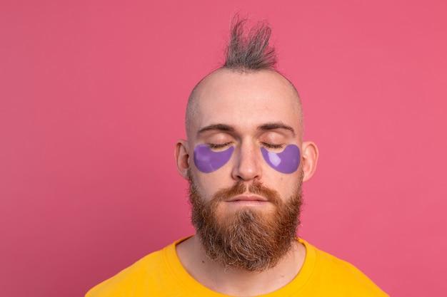 Hombre barbudo guapo europeo en camiseta amarilla y máscara de parches de ojos morados en rosa