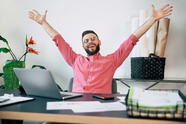 Hombre barbudo guapo feliz emocionado en ropa casual está sonriendo y gritando debido a ganar en algún trabajo, apuesta o lotería
