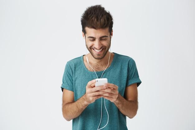 Hombre barbudo hispano positivo en elegante camiseta azul, buen peinado y barba, escuchando música con auriculares y mirando a través de las redes sociales en su teléfono celular.