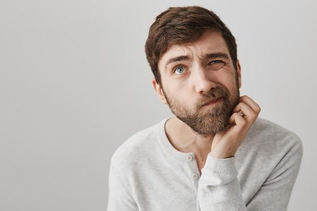 Hombre barbudo indeciso pensativo rascarse la barba y mirando hacia arriba pensando