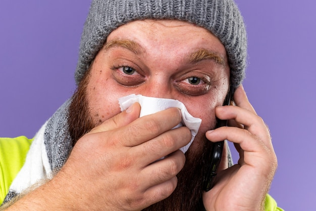 Hombre barbudo insalubre con sombrero y bufanda caliente alrededor del cuello que se siente terrible que sufre de gripe hablando por teléfono móvil que sopla la nariz que gotea estornudando en un pañuelo de papel sobre una pared púrpura
